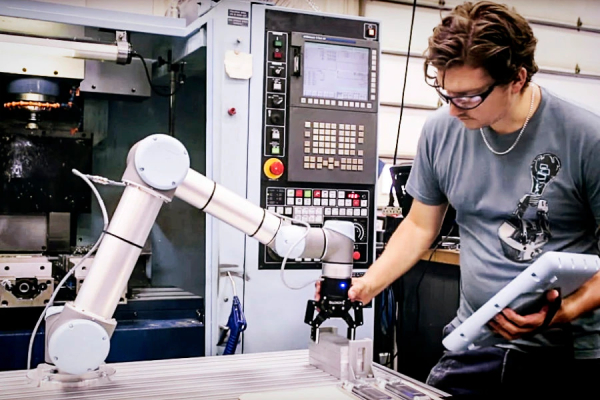 A Man Working With Collaborative Robot In An Industrial Sector.